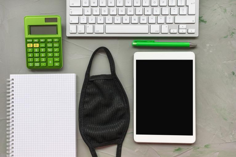 Work station with mask, notepad, tablet, keyboard, and green calculator